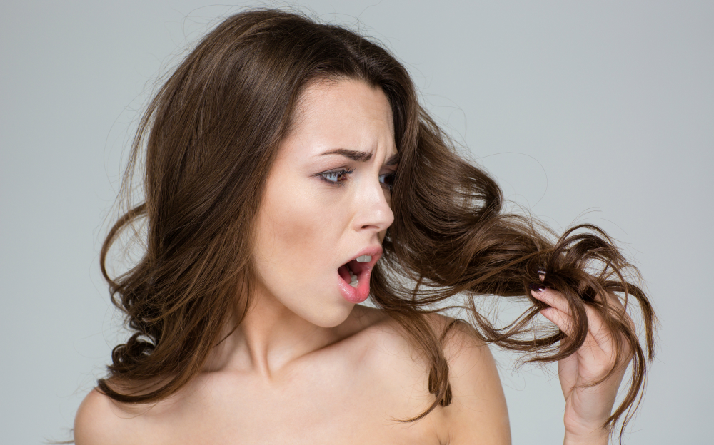 Beauty portrait of a disappointed  woman looking at her hair over gray background