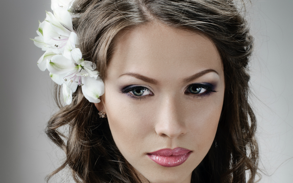 portrait of beautiful bride with flowers in hair on grey